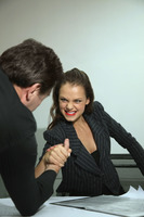 Businessman and businesswoman arm wrestling on table
