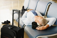 Businessman asleep on seat in airport lounge
