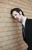 Businessman banging his head against the wall
