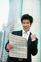 Businessman cheering while reading newspaper