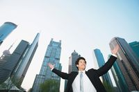 Businessman cheering with skyscrapers in the background
