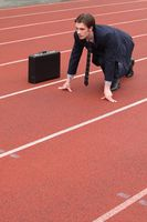 Businessman crouching on running track