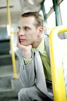 Businessman daydreaming while sitting in the bus