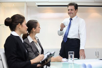 Businessman drinking coffee while talking to businesswomen in a meeting