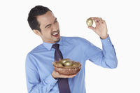 Businessman examine a golden egg