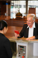 Businessman handing airline check-in attendant his passport upon arrival