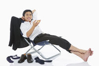 Businessman holding a drink while lying on a chair