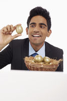 Businessman holding a gold egg