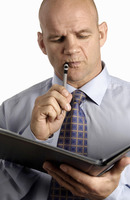 Businessman holding a pen and document thinking