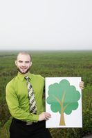 Businessman holding a tree sign