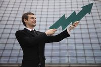 Businessman holding an arrow pointing up