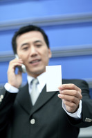 Businessman holding business card while talking on the phone