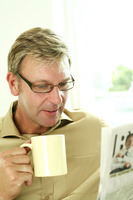 Businessman holding cup while reading newspaper