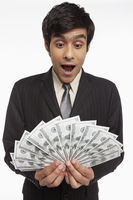 Businessman holding money, looking surprised