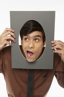 Businessman holding up a cut out cardboard with hole, making faces