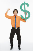 Businessman holding up a dollar sign, cheering