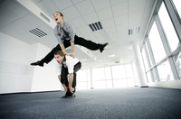 Businessman jumping over his colleague