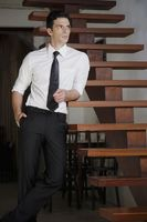 Businessman leaning against the stairs and looking away