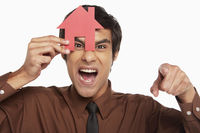 Businessman looking through a cut out house while pointing at the camera