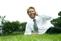 Businessman lying on the field talking on the phone