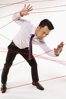 Businessman making his way through tangled wires