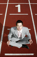 Businessman meditating on a running track