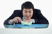 Businessman playing with a paper boat