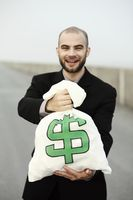 Businessman posing with a bag of money