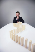 Businessman posing with wooden blocks arranged on the table