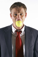 Businessman's mouth being stuffed with a tennis ball