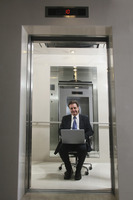Businessman sitting on office chair and using laptop in elevator