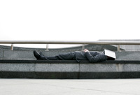 Businessman sleeping on the bench with a book covering his face