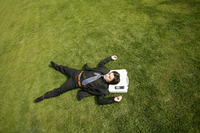 Businessman sleeping on the field with his head on the bag