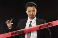 Businessman standing behind 'danger' tape, holding scissors