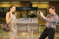 Businessman taking a picture of businesswoman using mobile phone, airline check-in attendant pointing at them