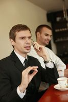 Businessman talking on the phone while his colleague smiling in the background