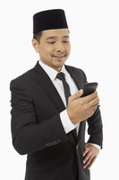 Businessman text messaging on his mobile phone
