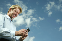 Businessman text messaging on the mobile phone