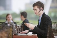 Businessman using laptop and credit card to shop online at outdoor cafe