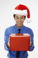 Businessman wearing santa hat and holding a gift box