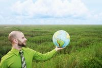 Businessman with arm outstretched holding a globe