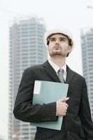 Businessman with hard hat holding a file at a construction site