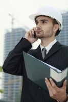 Businessman with hard hat talking on the phone and holding a file