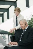Businessman with telephone headset using laptop, another businessman pointing at the screen