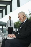 Businessman with telephone headset using laptop