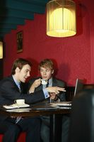 Businessmen having discussion and using laptop