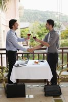 Businessmen shaking hands and toasting red wine