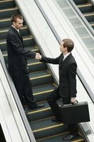 Businessmen shaking hands on escalator
