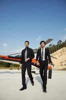 Businessmen walking away from helicopter