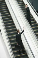 Businessmen waving at each other on escalator